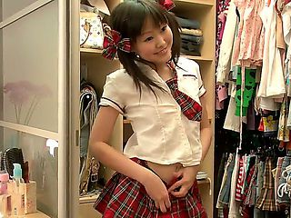 Petite and super cute Asian schoolgirl Aliona dresses up in the school uniform in front of the ca...