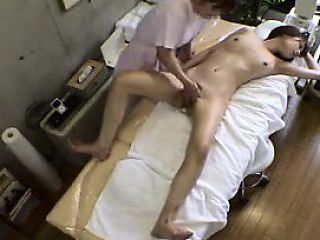 Petite Asian girl lies naked on the massage table and is ma