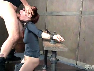 Belted neck and bound hands of a submissive redhead