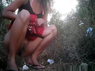 Long skirt woman pissing outside