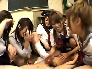 Asian schoolgirls play in a classroom and share a dick to c