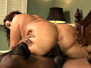 Curvaceous brunette cougar has wild sex with a black bull on the bed